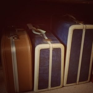 Three vintage hard suitcases in navy and brown