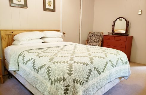 Queen size bed with green quilt in cottage bedroom with simple furniture