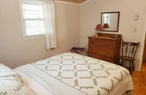 Cottage bedroom with queen size bed and green quilt with cedar plank ceiling