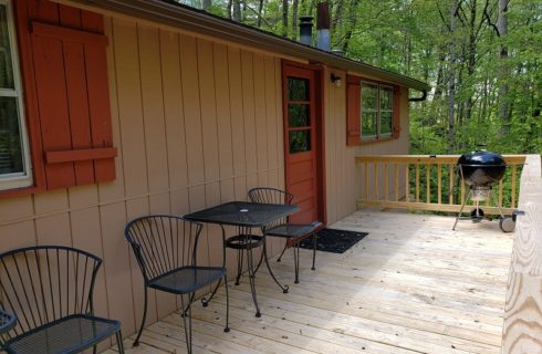 red shutters on a tan house with large deck, black cafe tables and chairs and charcoal grill