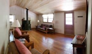 Cottage living area with large wood burning stove, southwest covered futon and cedar plank ceiling