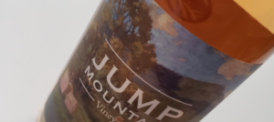 Bottle of Jump Mountain Vineyard's Mountain Mist Rose with watercolor bucolic landscape label