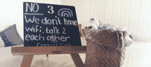 Small Table Top chalkboard easel that reads no we don't have wifi, talk to each other. Burlap bag with white flowers beside board