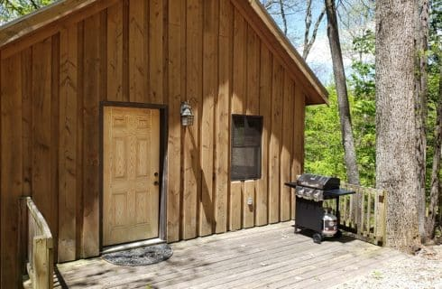 Hand hewn timber A-Frame cabin in the woods with propane grill on front porch
