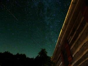 Rural night sky full of stars with a partial log structure off to the side