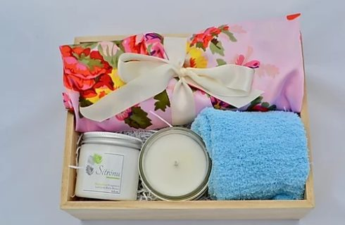 Wooden box with body cream, soy candle, pink floral robe, and fleece socks