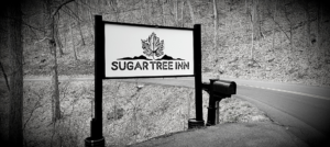 Black and white road sign for Sugar Tree Inn logo a sugar maple leaf over the mountains