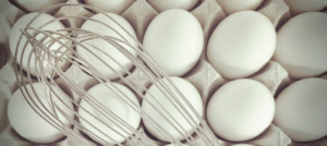 Eggs in a tray with silver whisk on top of eggs