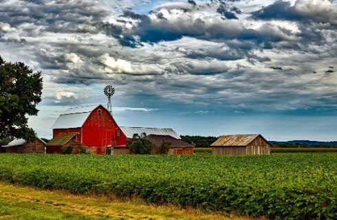 Large red barn next to other farm outbuildings in a green crop with a cloudy blue sky above.