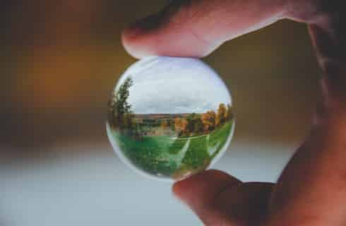 A small circular glass marble with a landscape scene being held between two fingers.