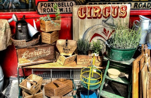 A vendor's set up at an antiques market selling vintage wooden boxes, greenery and a circus sign.