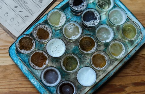 A rectangular silver tray holding 20 small glasses of with a variety of beers in different shades of brown.