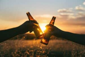 bottles toasting in a field in front of the sunset