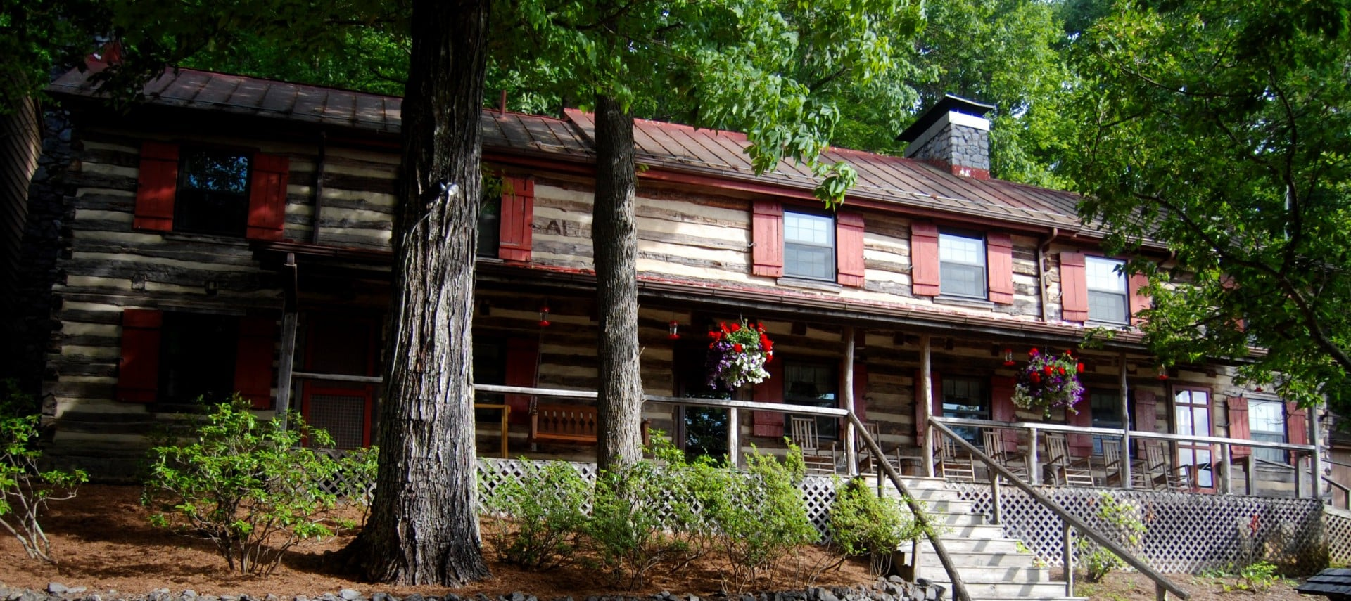 Front view of a long log cabin with red shuttered windows and an expansive front porch with stairs.
