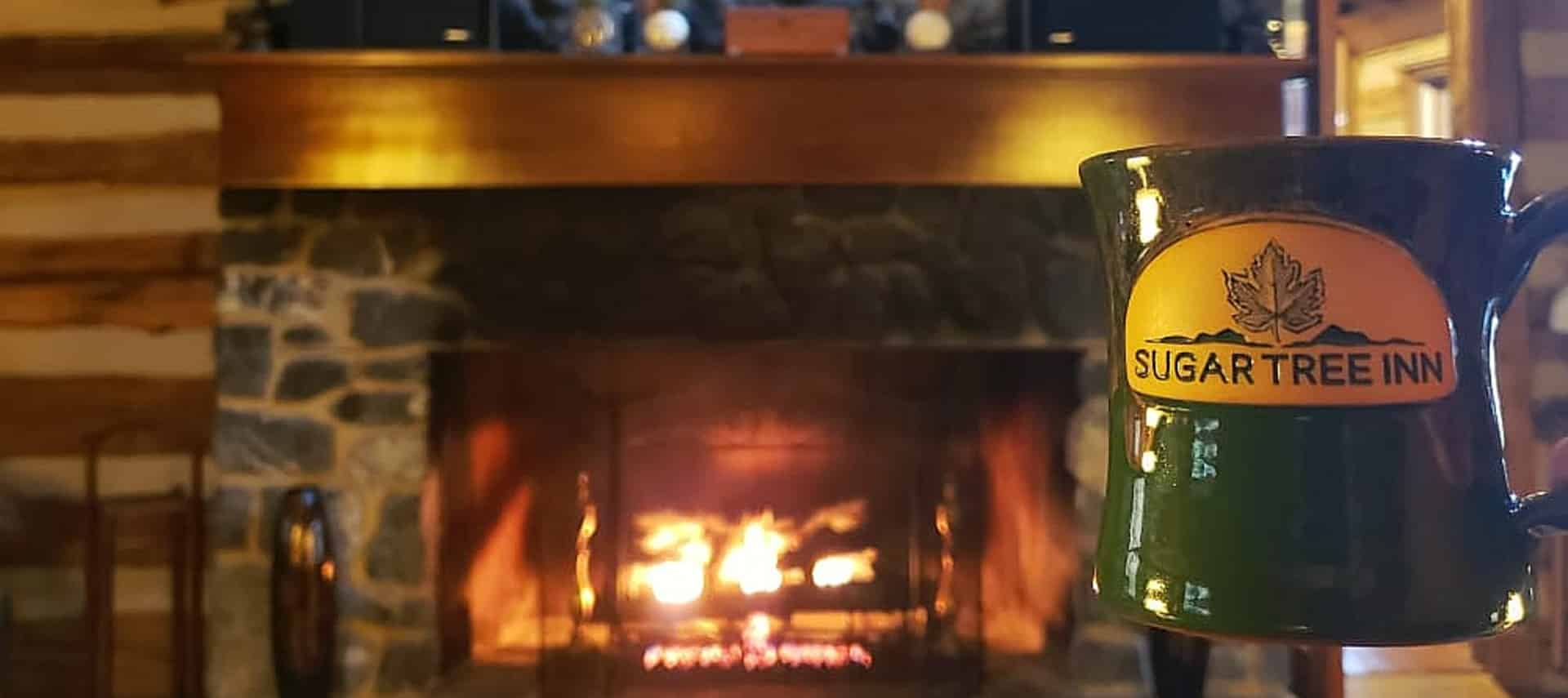 A roaring fire in a stone fireplace with a dark green mug with text Sugar Tree Inn in the foreground.