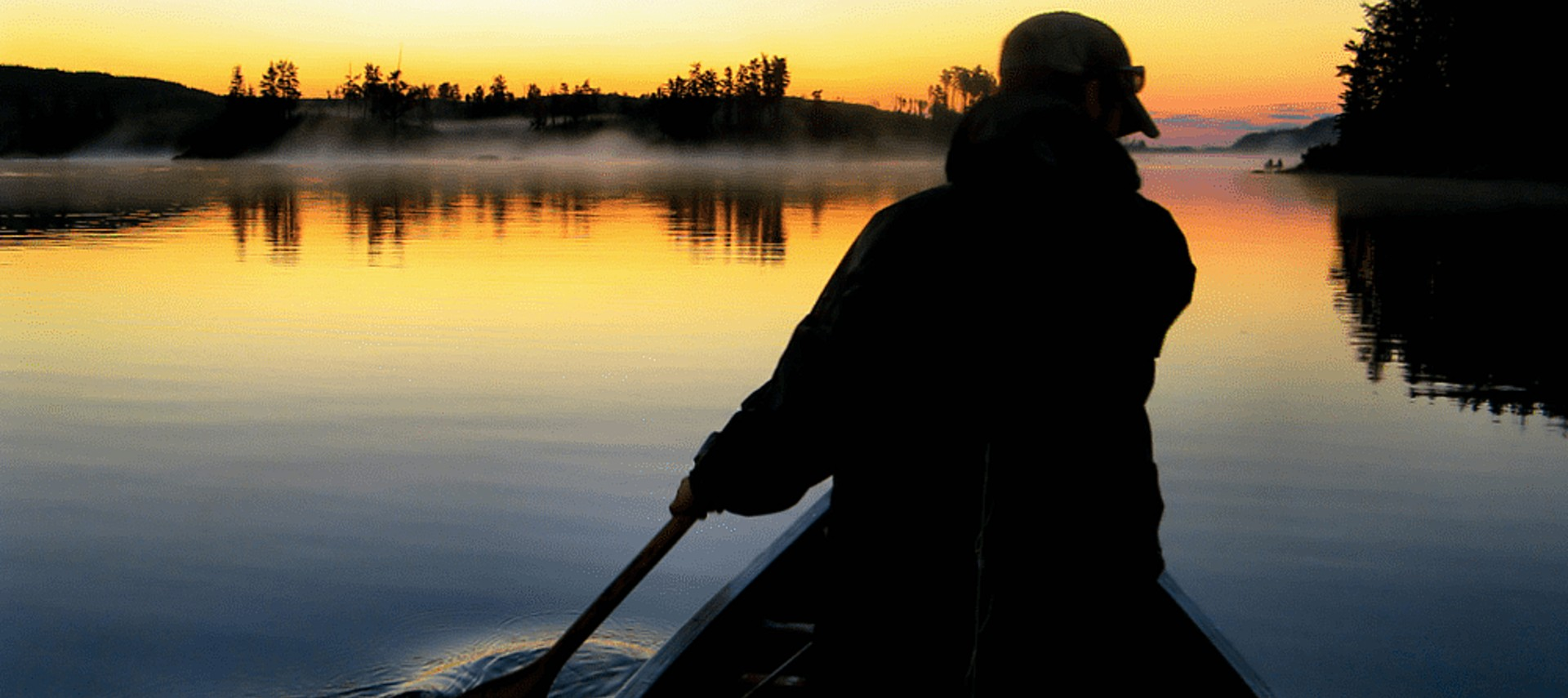 Dark silhouette of a person in a canoe rowing on a very calm lake at dusk.
