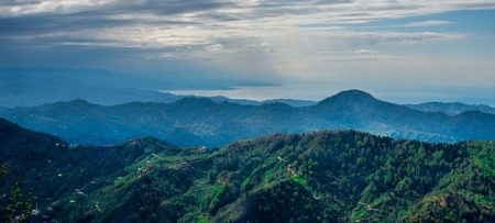 A beautiful landscape of a lush green mountain range against a blue cloudy sky.