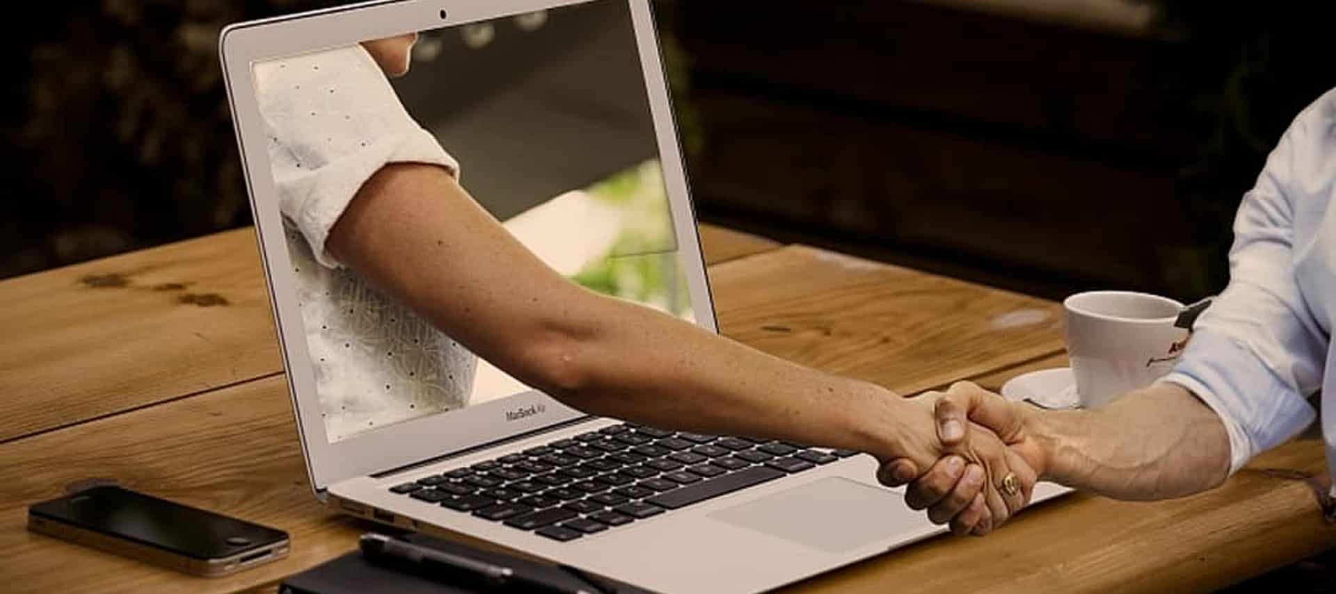 An arm coming out of a computer screen sitting on a brown table to shake the hand of a person in a blue shirt.