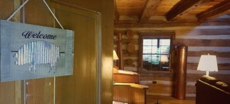 An open front door with a silver Welcome sign showing the inside of a spacious wood cabin.