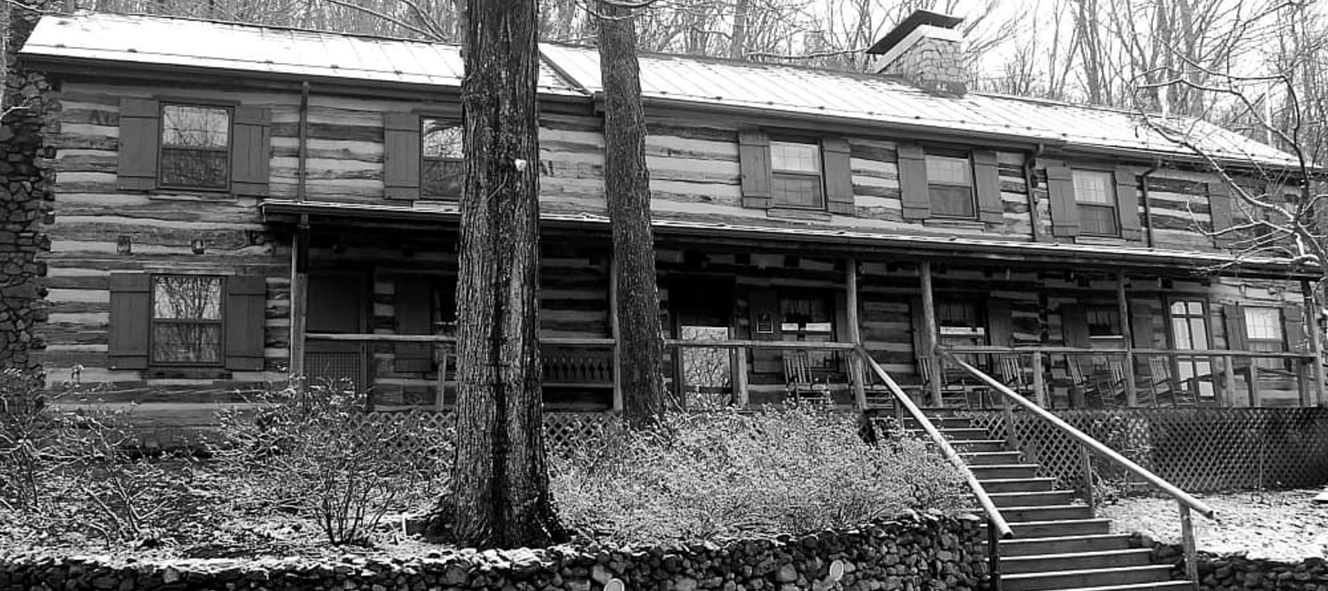 Outside of a large log cabin with lots of windows and a large porch in black and white format.