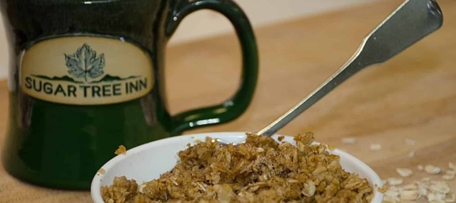 A delicious bowl of homemade oatmeal in a white bowl next to a dark green mug with text Sugar Tree Inn.
