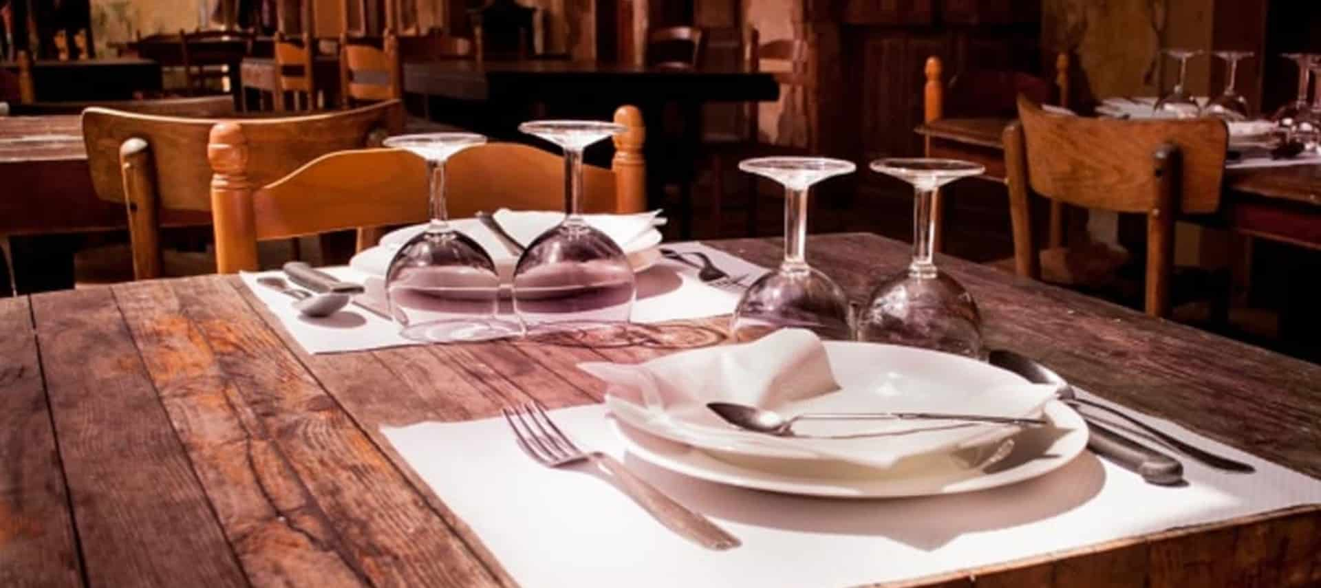 A rustic brown table in a restaurant with white linens, white plates, and clear glasses set for two.