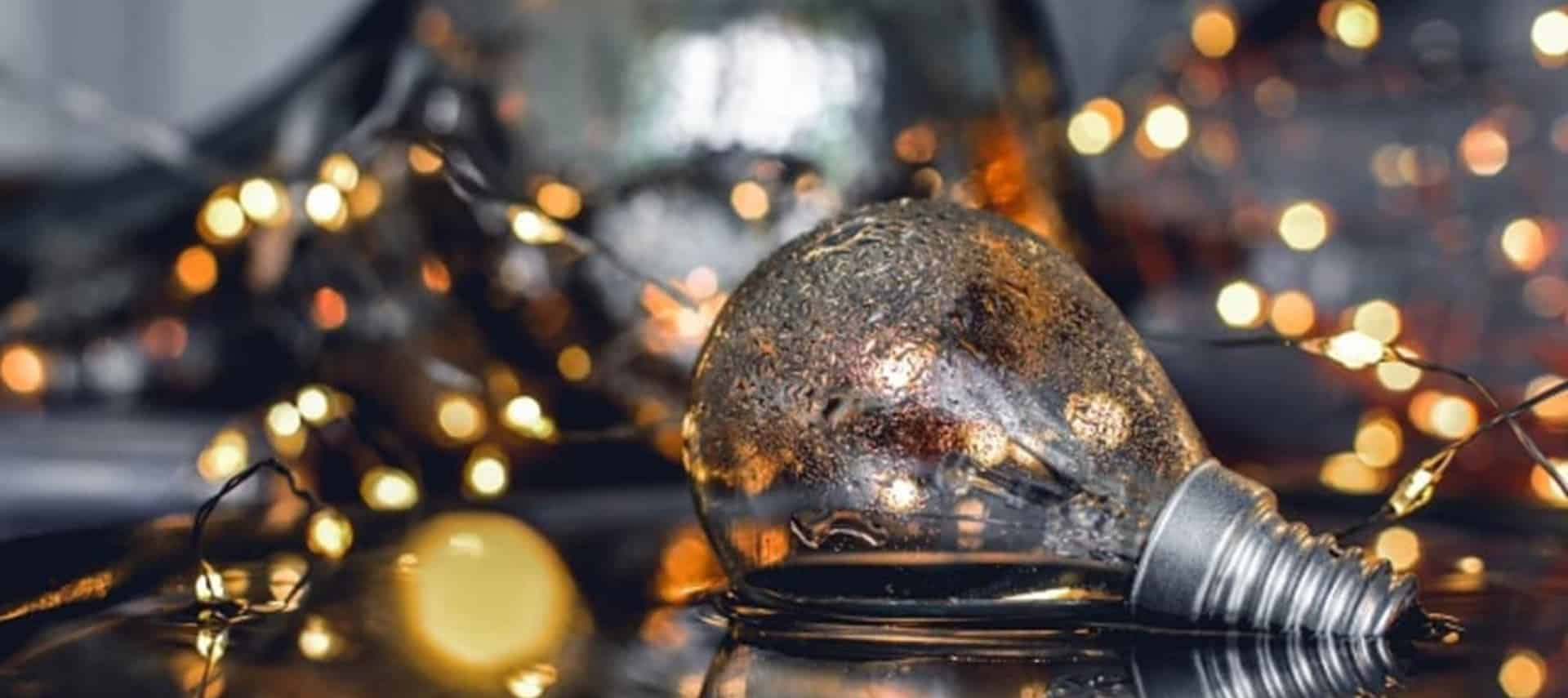 A brushed silver lightbulb laying on a table next to tiny white Christmas lights.