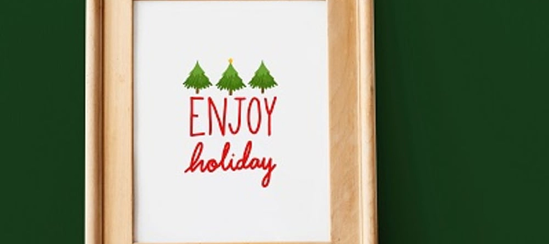 A light brown frame with a white image showing three Christmas trees and the text Enjoy Holiday in red.