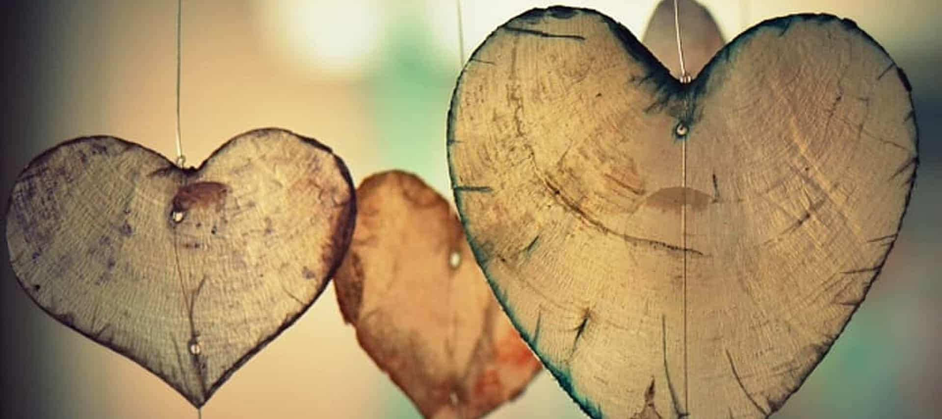 Three thinly sliced pieces of wood in heart shapes hanging by a thin silver wire.