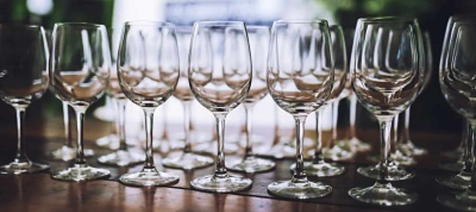 A dark brown table holding numerous empty crystal clear tall glasses of wine.