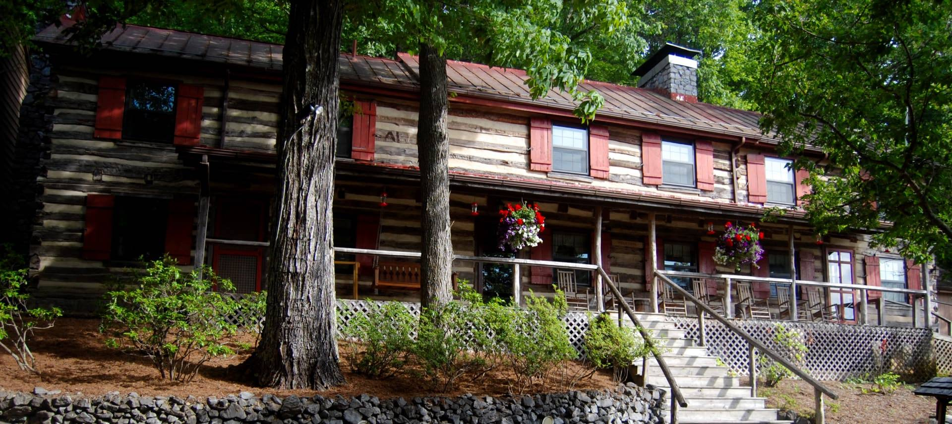 Exterior view of home that looks like a log cabin with brownish red shutters, long porch, and wooden rocking chairs surrounded by tall trees