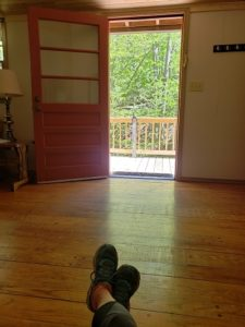 Cottage door open with view of forest, tennis shoe feet crossed in the foreground