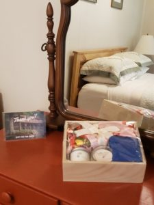 Sitronu spa gift set on dresser with queen bed with rustic quilt reflected in dresser mirror