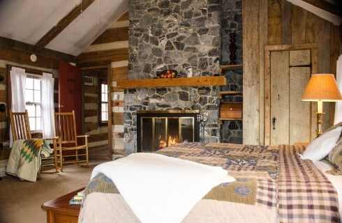 Guest room with high pitched ceiling and large stone floor to ceiling fireplae with roaring fire with large bed covered in neautral colored quilt and linens.