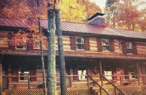 Large two story log cabin house in fall with chimney, burnt sienna shutters and large wood front porch with long set of stairs.