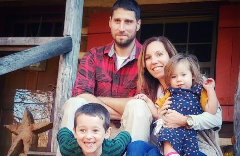 Family with dad in red and black plaid shirt, mom in neutral cream long sleep shirt and sweather and two children in fall colors sitting together on rustic wooden porch.