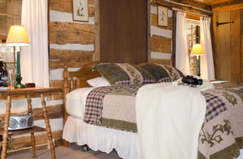 Bedroom with green, blue, and cream corduroy bedding, white blanket, birding book, binoculars, and wooden nightstand with radio, lamp, and alarm clock