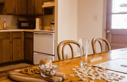Wooden table with Scrabble game, glass bowl with nuts, pretzels, apple and view into kitchen with stove and microwave