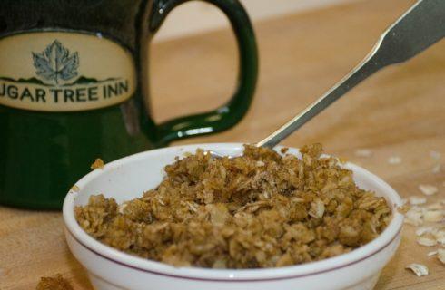 White ceramic bowl of warm cinnamon oatmeal next to hunter green Sugar Tree Inn mug on light wood table.