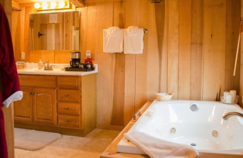 Bathroom with light wooden walls and vanity, tiled floor, tub with jets, mirror, and hanging white towels