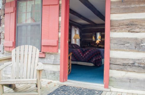 Patio of a log cabin with a brown Adirondack chair and an open red-framed door showing the inside of a guest room.