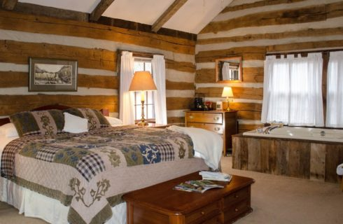 A spacious log cabin room with a queen bed, brown furniture and jacuzzi tub underneath a window with white curtains.