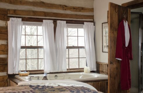 A log cabin room with a quilted bed, jacuzzi tub underneath a bright window with white curtains, and a dark red robe hanging on a bathroom door.