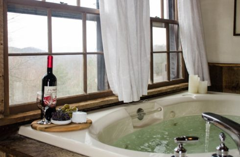 A jacuzzi tub full of water next to a bright window with white curtains and a brown tray holding a bottle of wine, glasses and snacks.
