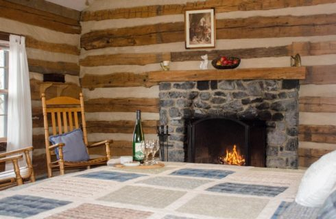 A log cabin room with a bed in a blue and white quilt in front of a dark grey stone fireplace.