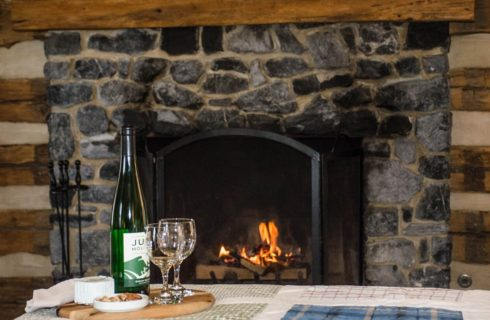 A glowing fire in a dark stone fireplace with a brown tray holding a bottle of wine and glasses on a bed in front of the fire.