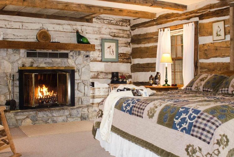 Bedroom with green, blue, and cream corduroy bedding, wooden rocking chairs, and light gray stoned fireplace with wooden mantel