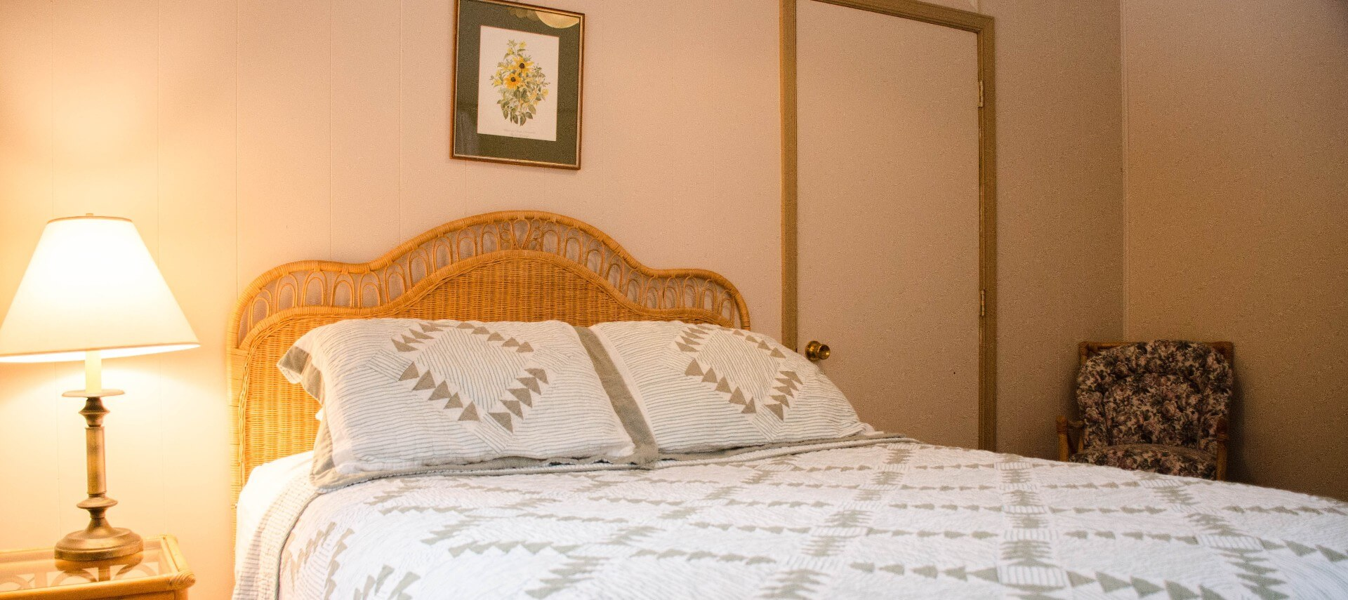 Bedroom with light brown wicker furniture, white and gray bedding, small chair, and lamp