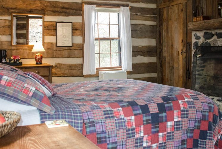 A log cabin room showing a queen bed in a red and blue quilt in front a dark grey stone fireplace.