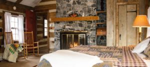 Spacious log cabin room with an impressive stone fireplace, queen bed and brown rocking chairs.